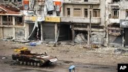 Sebuah tank yang hancur terlihat teronggok di jalanan wilayah al-Qossur propinsi Homs, Suriah (13/5). Pasukan Suriah dikabarkan telah kembali menguasai penuh sebuah kota dekat jalan raya yang menghubungkan ibukota Damaskus dengan Yordania.