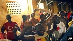 Des partisans d'Alpha Condé célébrant sa victoire au quartier général de son parti, à Conakry