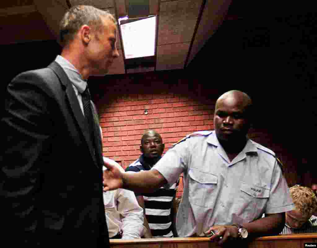 Oscar Pistorius is escorted by police at his court appearance in Pretoria, South Africa, February 15, 2013.