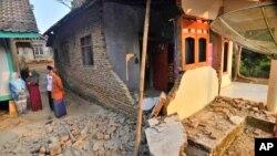 Warga berbincang dekat sebuah rumah yang rusak akibat gempa di Mandalawangi, Banten, Sabtu, 3 Agustus 2019. (Foto: AP)