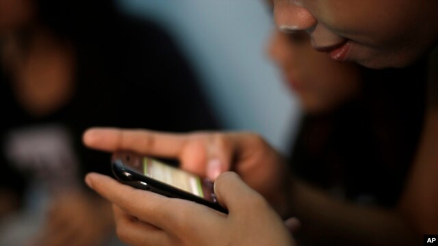 A teenage sex worker checks messages on her mobile phone at a boarding house in Bandung, West Java, Indonesia, Aug. 1, 2013.