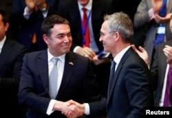 Makedonski ministar vanjskih poslova Nikola Dimitrov se rukuke sa generalnim sekretarom NATO saveza Jensom Stoltenbergom za vrijeme ceremonije potpisivanja protokola o pristupu Makedonije u NATO, Brisel, 6. februar