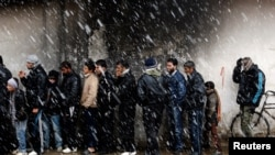 Men wait to buy bread in front of a bakery shop in Syria. (file)