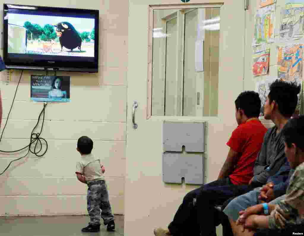 A detained immigrant child watches a cartoon while awaiting the arrival of U.S. first lady Melania Trump with other young detained immigrants at a U.S Customs and Border patrol immigration detainee processing facility in Tucson, Arizona.