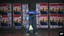 Seorang wanita berjalan melewati sebuah tembok yang tertutup poster kampanye Presiden Hugo Chavez sebagai calon Presiden, dalam Pemilihan Presiden Venezuela di Caracas (Foto: dok). Venezuela akan menggelar Pemilihan Presiden, Minggu ini (7/10).