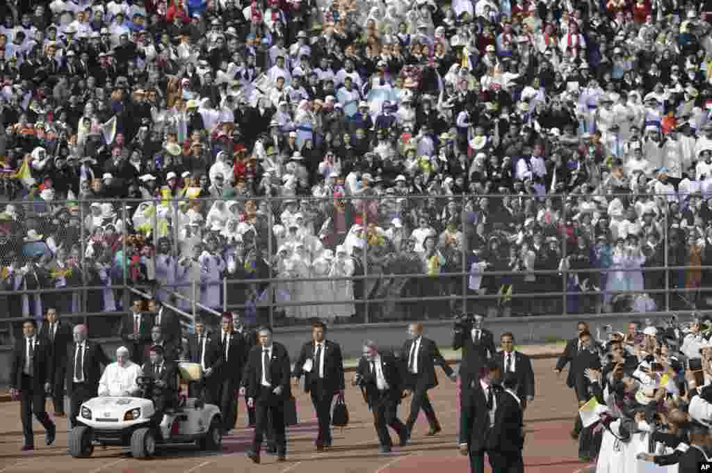 Pope Francis, followed by security guards, arrives to celebrate Mass at the Venustiano Carranza stadium in Morelia, Mexico.