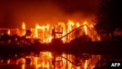 2018年7月27日,在美国加利福尼亚州雷丁市的卡尔火灾中,燃烧的房屋在水池留下倒影。