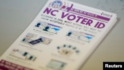 A pile of government pamphlets explaining North Carolina's controversial voter ID law sits on table at a polling station.