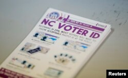 """FILE - A pile of government pamphlets explaining North Carolina's controversial """"Voter ID"""" law sits on table at a polling station."""