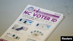 "FILE - A pile of government pamphlets explaining North Carolina's controversial ""Voter ID"" law sits on table at a polling station."