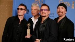 "Adam Clayton (L), Bono (2nd from R), Larry Mullen, Jr. and The Edge (R) from the band U2 pose backstage with their award for Best Original Song for"" Ordinary Love"" from the film ""Mandela: Long Walk to Freedom"" , Jan. 12, 2014."