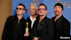 FILE - Adam Clayton (L), Bono (2nd from R), Larry Mullen, Jr. and The Edge (R) from the band U2 pose backstage with their award for Best Original Song, Jan. 12, 2014.
