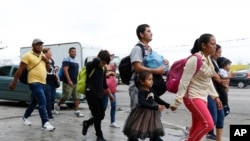 Migrantes en San Pedro Sula, Honduras, caminan por una autopista cuando una caravana de cientos de personas parte hacia Estados Unidos con la esperanza de pedir asilo. Abril 10 de 2019.