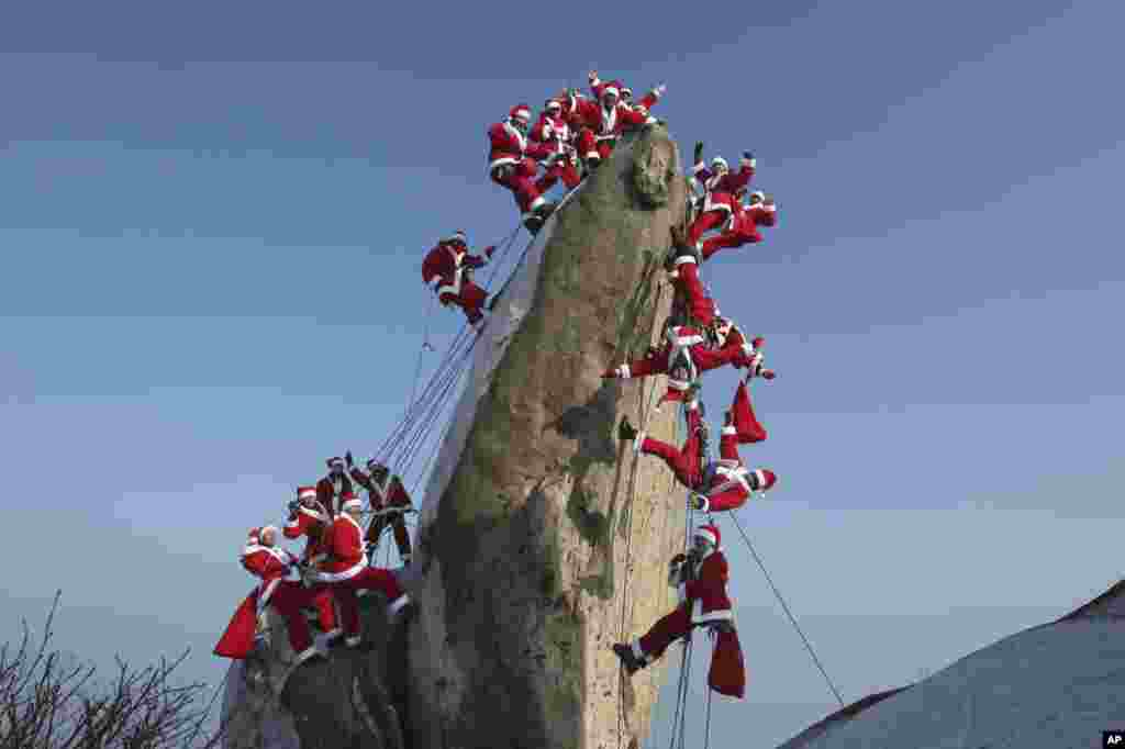 Mountain climbers in Santa Claus outfits pose during an event to hope for safe climbing and to promote Christmas charity on the Buckhan mountain in Seoul, South Korea.