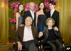 Actor Kirk Douglas (seated left) holds hands with his wife Anne Douglas as they pose with family members, their son Michael (standing second left), his wife Catherine Zeta-Jones (standing second right), and their children, Carys Zeta Jones (left) and son Dylan during Kirk's 100th birthday party at the Beverly Hills Hotel, Dec. 9. 2016, in Beverly Hills, Calif.