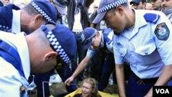Polisi Australia membubarkan perkemahan para pengunjuk rasa di taman-taman Australia. Seorang pengunjuk rasa dipindahkan oleh polisi saat masih duduk di dalam tendanya di Sydney, Australia (foto: dok).