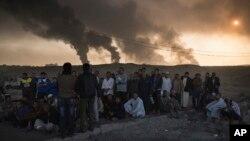 在摩苏尔以南的奎亚拉油田燃烧的同时,被伊拉克国家安全人员拘押的人在一个检查哨所接受审问(2016年11月5日)