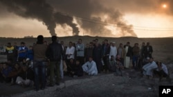 Men are held by Iraqi national security agents, to be interrogated at a checkpoint, as oil fields burn in Qayara, south of Mosul, Iraq, Nov. 5, 2016. Islamic State fighters are launching counterattacks in the thin strip of territory Iraqi special forces have recaptured in eastern Mosul.