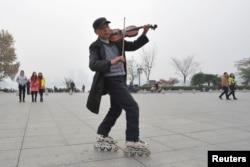 一位穿着旱冰鞋的男士在雾霾笼罩下的南京市的一座广场上拉着小提琴。(2013年12月5日)