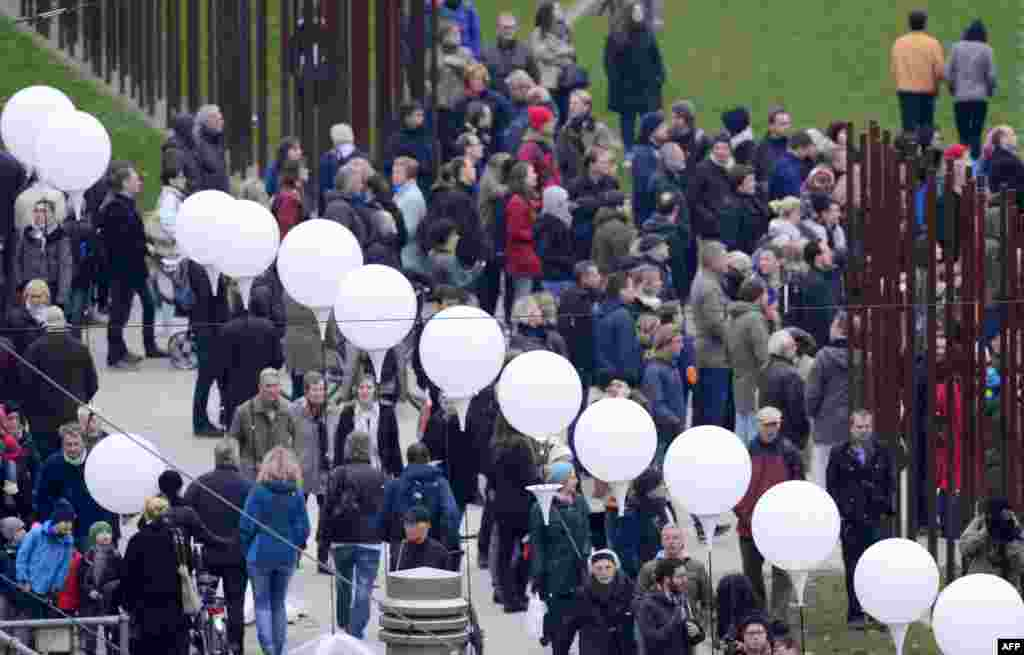 People gather along a light installation called Light Border ( Lichtgrenze ) featuring the Berlin Wall during commemorations to mark the 25th anniversary of the fall of the Berlin Wall at the Berlin Wall Memorial in the Bernauer Strasse Berlin, Germany.