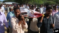 FILE - Somalis and local journalists carry the body of Moqtar Mohamed Hirab for burial in Mogadishu, Somalia.