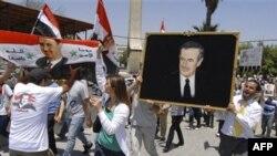 Hàng ngàn ủng hộ viên cầm cờ và ảnh của ông Assad tuần hành tại thủ đô Damascus, ngày 21/6/2011
