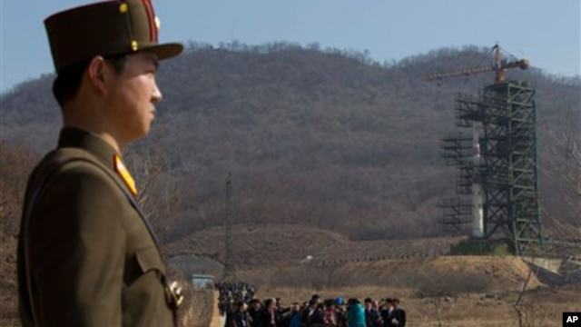 A crowd of media gather around a North Korean official on a road in front of North Korea's Unha-3 rocket, slated for liftoff between April 12-16, stands at Sohae Satellite Station in Tongchang-ri, North Korea, April 8, 2012