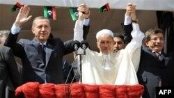 Ông Mastafar Abdel Jalil, giữa, Thủ tướng Thổ Nhĩ Kỳ Recep Tayyip Erdogan, trái, và Bộ trưởng Ngoại giao Thổ Nhĩ Kỳ Ahmet Davutoglu chào đám đông ở Tripoli, Libya, Thứ Sáu 16/9/2011