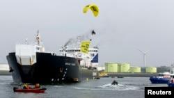 """Anggota Greenpeace melayang membawa spanduk berbunyi """"No Arctic Oil"""", di atas tanker minyak Rusia Mikhail Ulyanov di pelabuhan Rotterdam 1/5/2014."""