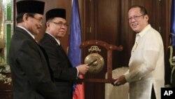 Tổng thống Philippines Benigno Aquino III (phải) nhận chiếc cồng của Chủ tịch Mặt trận Giải phóng Hồi giáo Moro trước khi ký một thỏa thuận khung lịch sử vào năm 2012