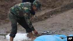 Binh sĩ Lào cạnh một thi thể của nạn nhân vụ tai nạn máy bay bên bờ sông Mekong ở Pakse, Lào, ngày 18/10/2013.