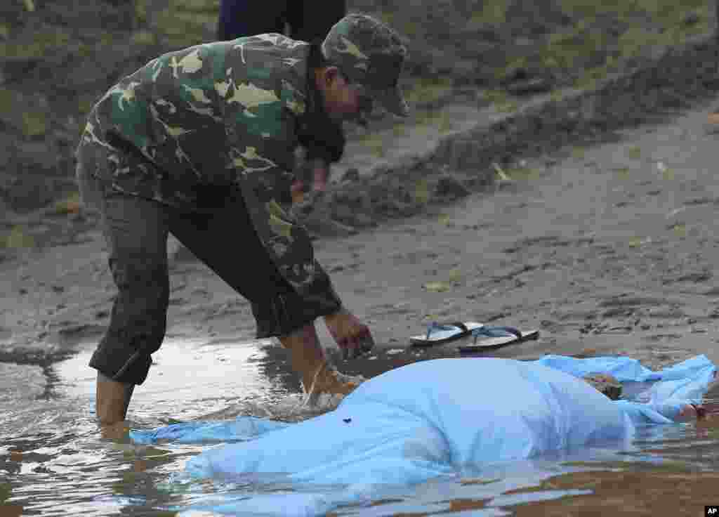 A Laotian soldier covers the body of a plane crash victim with a sheet on the bank of the Mekong River in Pakse, Laos, Oct. 18, 2013.