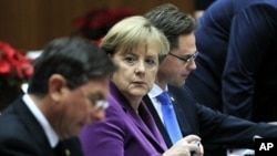 Slovenia's Prime Minister Barut Pahor (L), Germany's Chancellor Angela Merkel (C) and Finland's Prime Minister Jyrki Katainen attend a European Union summit in Brussels December 9, 2011.