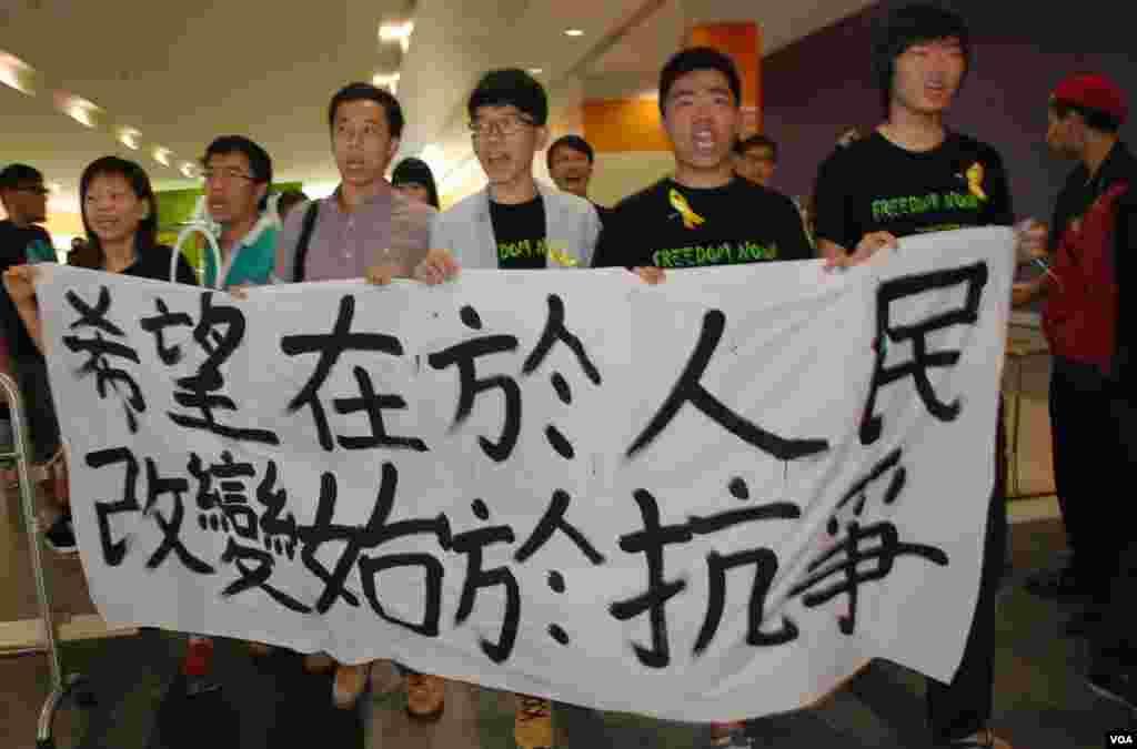 民陣及學聯成員拉起橫額,在李飛出席政改簡介會的亞洲博覽館內示威
