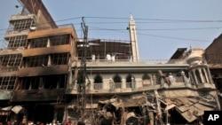 Nhân viên cứu hộ, cảnh sát và thường dân tụ tập tại hiện trường vụ nổ bom xe hơi ở Peshawar, Pakistan, ngày 29/9/2013.