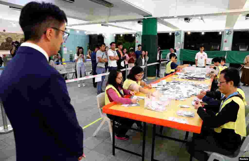 Un candidato local observa a los funcionarios que cuentan votos en una mesa electoral en Kowloon Tong, Hong Kong, China, 24 de noviembre de 2019.
