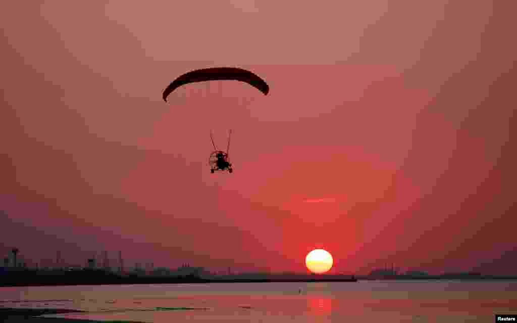 A man flies his powered paraglider over Marquette Beach as the sun sets in Gary, Indiana, USA, Sept. 6, 2013.