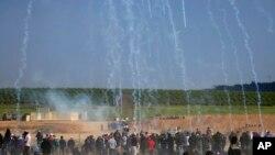 اسرائیلی فوجیوں کی جانب سے جمعے کو غزہ میں مظاہرین پر کی جانے والی آنسو گیس کی شیلنگ کا ایک منظر