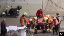 In this image made from video, emergency rescue workers stretcher an unidentified person at the site of an explosion at a metro station in Brussels, Belgium.