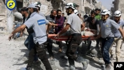 Sept. 21, 2016, file photo, provided by the Syrian Civil Defense White Helmets, rescue workers work the site of airstrikes in the al-Sakhour neighborhood of the rebel-held part of eastern Aleppo, Syria.
