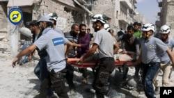 Petugas menyelamatkan para pekerja di lokasi yang terkena serangan udara di daerah al-Sakhour di Aleppo, Suriah (21/9).