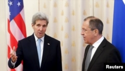 Menteri Luar Negeri AS John Kerry (kiri) berbicara pada Menteri Luar Negeri Rusia Sergei Lavrov sebelum bertemu di Moskow, Rusia, 15 Desember 2015.