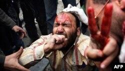 Protivnici egipatske vlade pomažu jednom od ranjenih u današnjim sukobima na kairskom trgu Tahrir