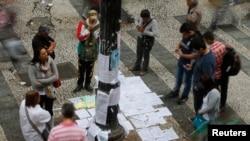 Người dân đứng xem danh sách việc làm trên 1 đường chính ở trung tâm thành phố Sao Paulo, 13/8/2014.