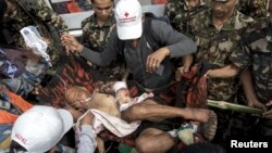 Nepal military personnel and aid workers carry earthquake victim Buddha Gurung on a stretcher after he arrives by helicopter from his village in Pokkara airport, April 30, 2015.