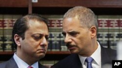U.S. Attorney General Eric Holder, right, and U.S. Attorney for New York's Southern District Preet Bharara confer at a news conference in New York, 20 Jan 2011