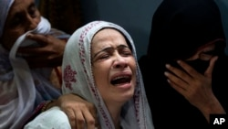 A Pakistani mother, center, mourns over the death of her son who was killed in a bomb explosion, in Karachi, Pakistan, Aug. 7, 2013