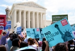 FILE - Protesters hold up signs and call out against the Supreme Court ruling upholding President Donald Trump's travel ban outside the the Supreme Court in Washington, June 26, 2018.