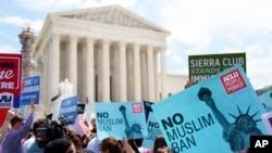 示威者2018年6月26日在美国联邦最高法院外高举标语,抗议最高法院支持美国总统川普旅行禁令的裁决。