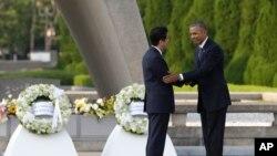 Le président américain Barack Obama serre la main du Premier ministre japonais Shinzo Abe devant le cénotaphe du Parc du mémorial de la Paix à Hiroshima, au Japon, vendredi 27 mai 2016